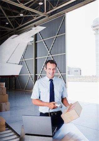 Worker scanning box in hangar Stock Photo - Premium Royalty-Free, Code: 635-03781353