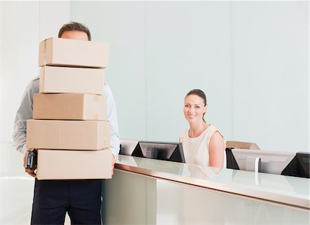 supply - Delivery man holding stack of boxes in reception area Stock Photo - Premium Royalty-Free, Code: 635-03781362