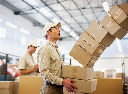 Worker dropping boxes in shipping area Stock Photo - Premium Royalty-Free, Code: 635-03781372