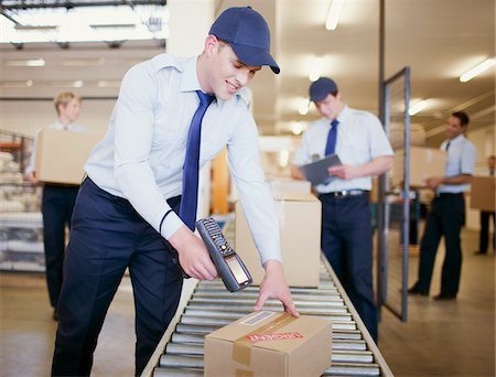 Worker scanning box on conveyor belt in shipping area Stock Photo - Premium Royalty-Free, Code: 635-03781386