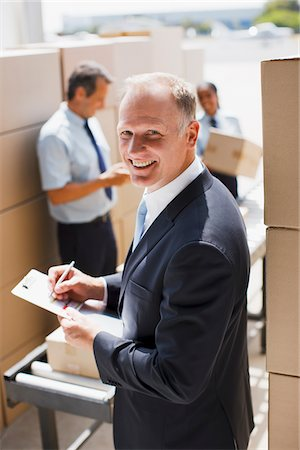 Supervisor writing on clipboard in shipping area Stock Photo - Premium Royalty-Free, Code: 635-03781397