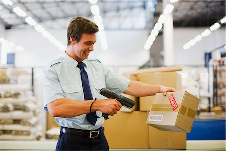 Worker scanning box in shipping area Stock Photo - Premium Royalty-Free, Code: 635-03781392
