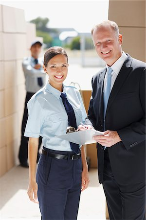 Supervisor with clipboard standing with worker in shipping area Stock Photo - Premium Royalty-Free, Code: 635-03781401