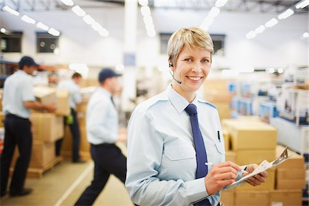 Worker with clipboard in shipping area Stock Photo - Premium Royalty-Free, Code: 635-03781419