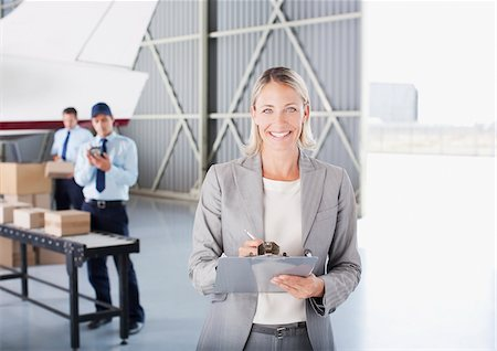 Supervisor writing on clipboard in hangar Stock Photo - Premium Royalty-Free, Code: 635-03781410