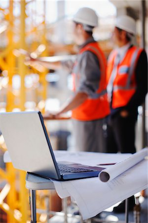 supervising - Construction workers behind laptop and blueprints on construction site Stock Photo - Premium Royalty-Free, Code: 635-03781444