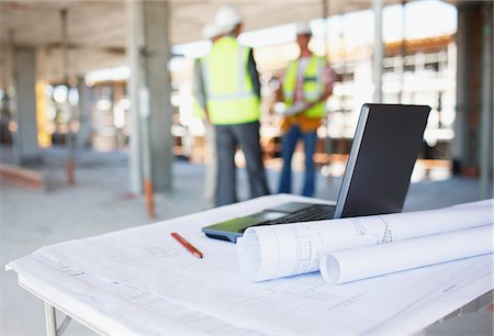 drawing computer - Construction workers behind blueprints and laptop on construction site Stock Photo - Premium Royalty-Free, Code: 635-03781462