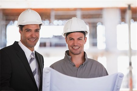 supervising - Construction worker and businessman looking at blueprints on construction site Stock Photo - Premium Royalty-Free, Code: 635-03781488
