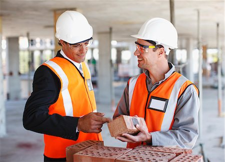 supervising - Construction workers looking at bricks on construction site Stock Photo - Premium Royalty-Free, Code: 635-03781491