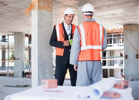 supervising - Businessman talking to construction worker on construction site Stock Photo - Premium Royalty-Free, Code: 635-03781504