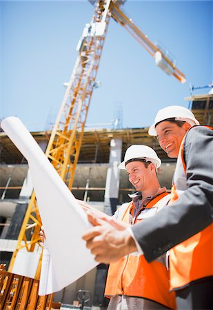supervising - Construction workers looking at blueprints on construction site Stock Photo - Premium Royalty-Free, Code: 635-03781509