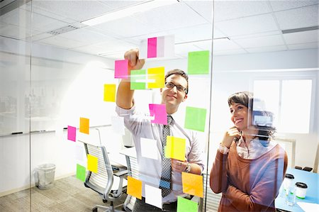 self adhesive note - Business people looking at adhesive notes in conference room Stock Photo - Premium Royalty-Free, Code: 635-03781525