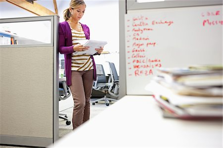 report - Businesswoman looking at paperwork in office Stock Photo - Premium Royalty-Free, Code: 635-03781531