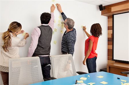 placing - Business people putting adhesive notes on conference room wall Stock Photo - Premium Royalty-Free, Code: 635-03781562