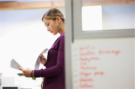 Businesswoman looking at paperwork in office Stock Photo - Premium Royalty-Free, Code: 635-03781593
