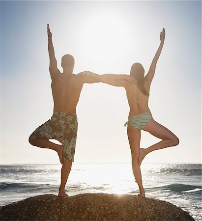 standing - Couple balancing on one foot together at beach Stock Photo - Premium Royalty-Free, Code: 635-03781712