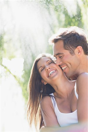Laughing couple hugging outdoors Stock Photo - Premium Royalty-Free, Code: 635-03781731