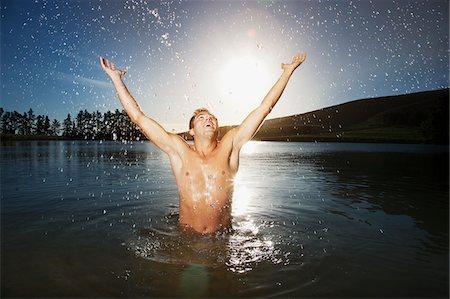 shirtless men - Excited man splashing water in lake Stock Photo - Premium Royalty-Free, Code: 635-03781745