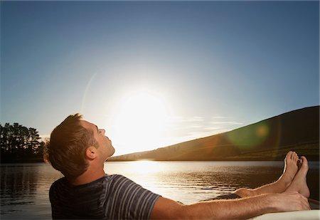 Man relaxing near lake at sunset Stock Photo - Premium Royalty-Free, Code: 635-03781751