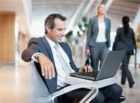 Businessman using laptop in airport Stock Photo - Premium Royalty-Free, Code: 635-03781856