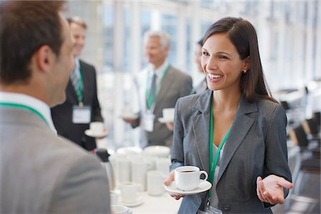 Businesswoman drinking coffee and talking to co-worker Stock Photo - Premium Royalty-Free, Code: 635-03781853