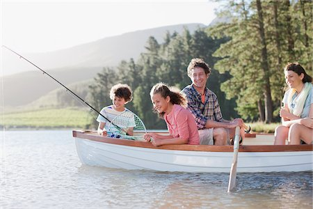 side view of person rowing in boat - Family fishing in boat on lake Stock Photo - Premium Royalty-Free, Code: 635-03859657