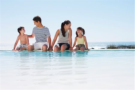 Family sitting with feet in infinity pool Stock Photo - Premium Royalty-Free, Code: 635-03859669