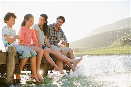 Family on dock splashing feet in lake Stock Photo - Premium Royalty-Free, Code: 635-03859690