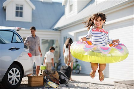 Girl with inflatable ring jumping in driveway Stock Photo - Premium Royalty-Free, Code: 635-03859707