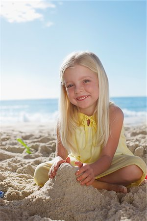 Girl making sandcastle on beach Stock Photo - Premium Royalty-Free, Code: 635-03859702