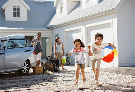 Brother and sister with beach ball running on driveway Stock Photo - Premium Royalty-Free, Code: 635-03859760