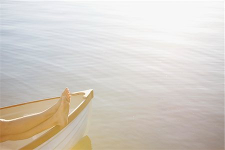 side view of person rowing in boat - Bare feet in rowboat on lake Stock Photo - Premium Royalty-Free, Code: 635-03859780