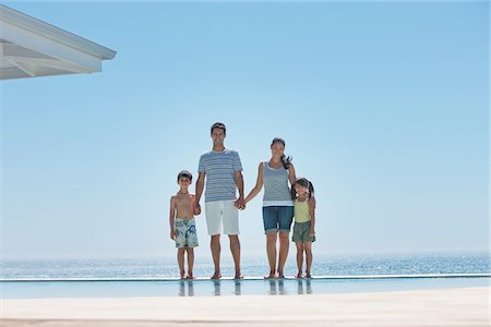 forever - Family standing at edge of infinity pool with ocean in background Stock Photo - Premium Royalty-Free, Code: 635-03859783
