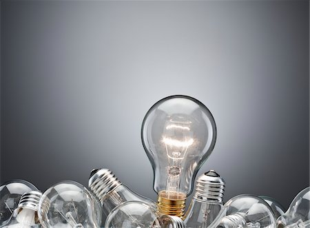 Illuminated light bulb in pile Stock Photo - Premium Royalty-Free, Code: 635-03859798