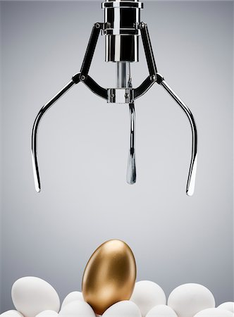Mechanical claw reaching for golden egg Stock Photo - Premium Royalty-Free, Code: 635-03859793