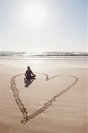 Woman sitting cross-legged in heart on beach Stock Photo - Premium Royalty-Free, Code: 635-03859817