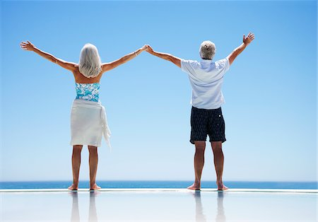 forever - Senior couple standing at edge of infinity pool with arms outstretched Stock Photo - Premium Royalty-Free, Code: 635-03859812
