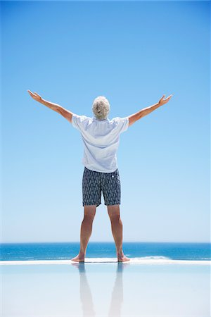 forever - Senior man with arms outstretched at edge of infinity pool Stock Photo - Premium Royalty-Free, Code: 635-03859824