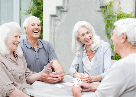 Senior couples playing cards on patio Stock Photo - Premium Royalty-Free, Code: 635-03859845