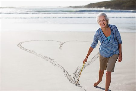stick - Senior woman drawing heart in sand Stock Photo - Premium Royalty-Free, Code: 635-03859848