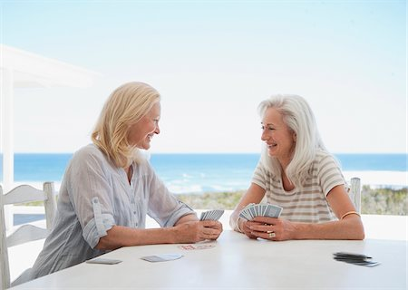 Senior women playing cards on beach patio Stock Photo - Premium Royalty-Free, Code: 635-03859882