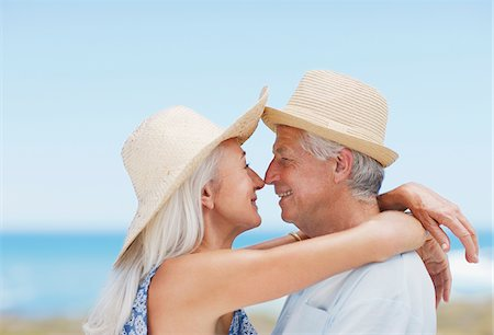 Senior couple in sun hats kissing on beach Stock Photo - Premium Royalty-Free, Code: 635-03859891