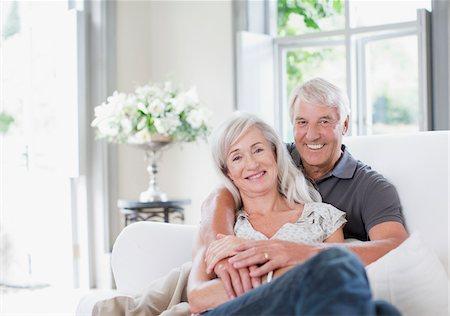 Senior couple hugging on sofa in living room Stock Photo - Premium Royalty-Free, Code: 635-03859906