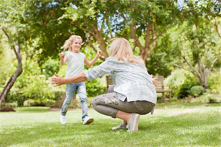 Granddaughter running toward grandmother in yard Stock Photo - Premium Royalty-Free, Code: 635-03859918