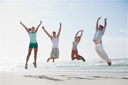 Couples jumping on beach Stock Photo - Premium Royalty-Free, Code: 635-03860138