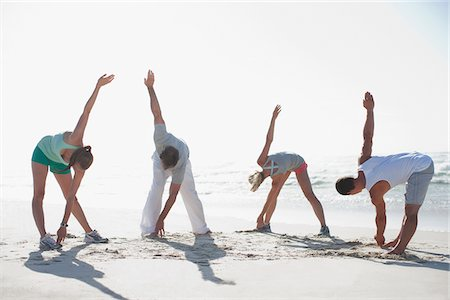 Friends stretching on beach Stock Photo - Premium Royalty-Free, Code: 635-03860167