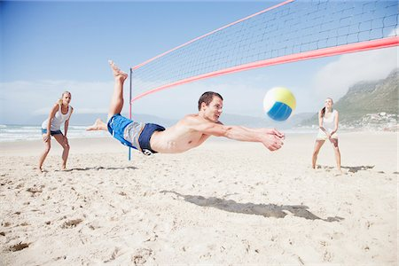 Friends playing volleyball on beach Stock Photo - Premium Royalty-Free, Code: 635-03860161