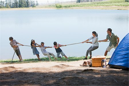 Family playing tug-of-war at campsite Stock Photo - Premium Royalty-Free, Code: 635-03860178