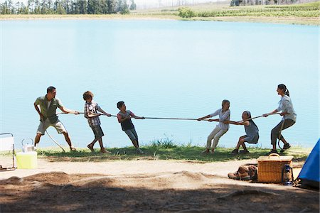 Family playing tug-of-war at campsite Stock Photo - Premium Royalty-Free, Code: 635-03860197