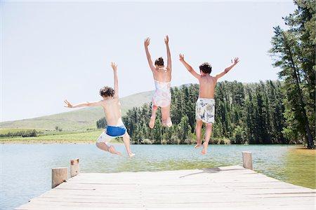 Kids jumping off dock into lake Stock Photo - Premium Royalty-Free, Code: 635-03860205